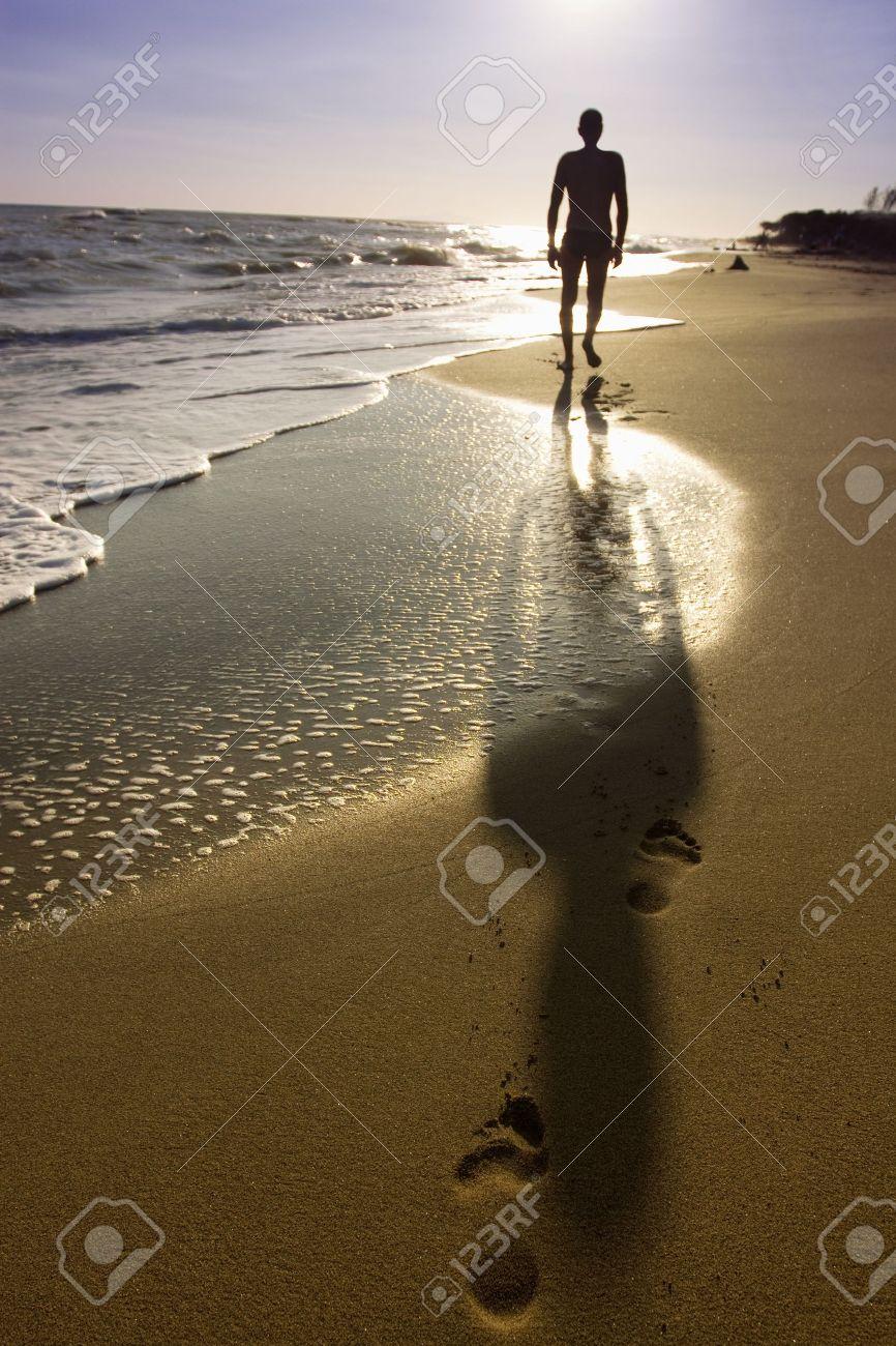 14523621-uomo-che-cammina-sulla-spiaggia-Archivio-Fotografico